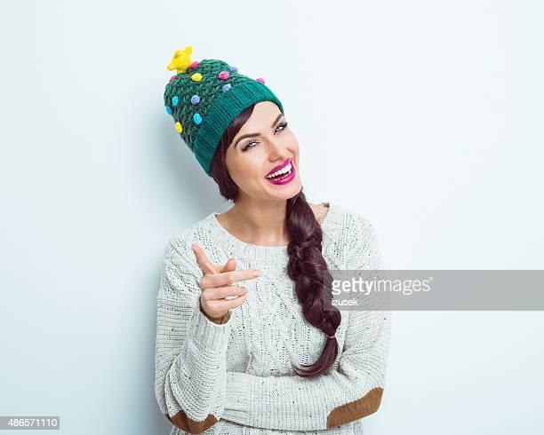 Heureuse femme en tenue d'hiver pointant à la caméra