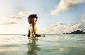 Happy woman in yellow bikini waist deep in sea.