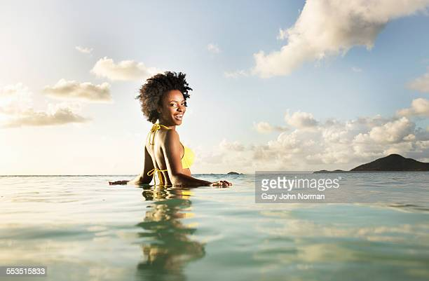 Happy woman in yellow bikini waist deep in sea.