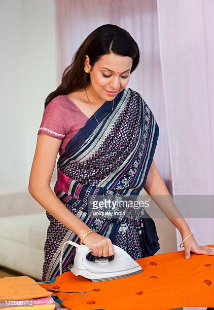 Happy woman ironing clothes at home