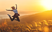Happy woman jumping and enjoying life in field at sunset in mountains