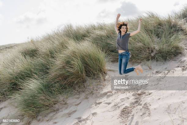Happy woman jumping in beach dune