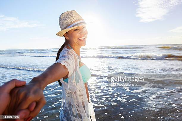 Happy woman leads husband into the ocean