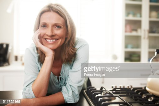 Happy woman leaning on kitchen counter