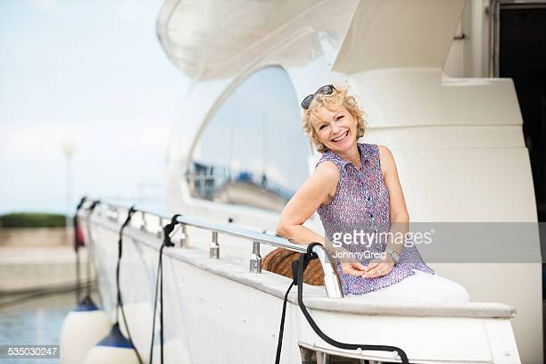 Happy Woman Leaning On Yacht Railing