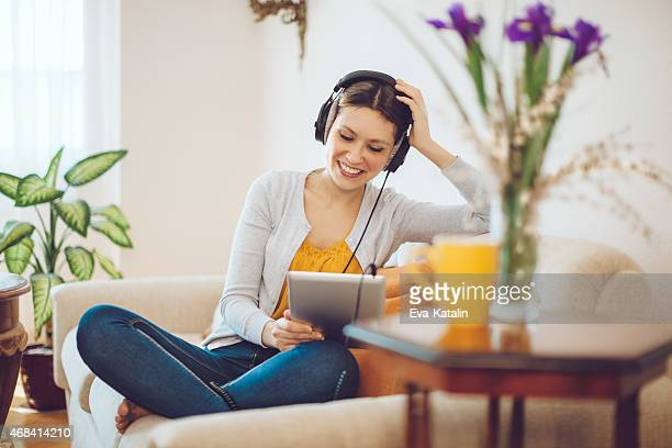 Happy woman listening to music at home