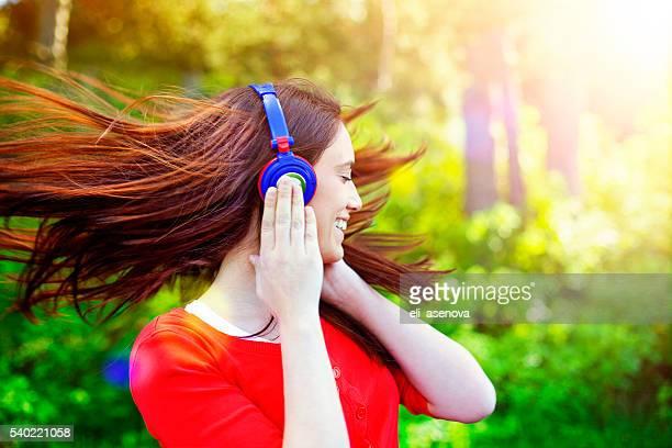Heureuse femme écouter de la musique et agitant cheveux