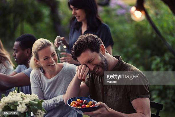 Happy woman looking at man rubbing eyes while holding tomato bowl at dinner party in yard
