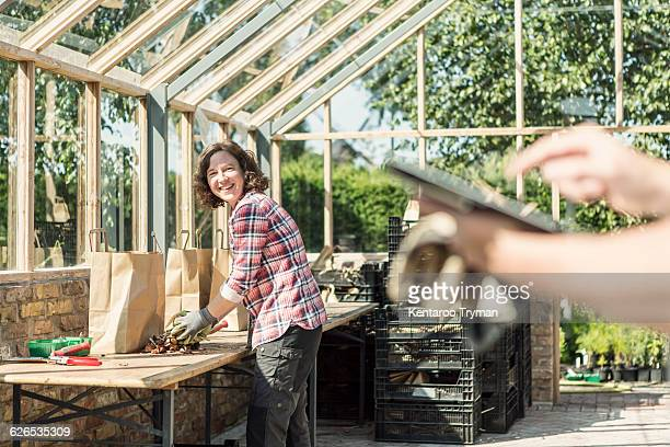 Happy woman looking at man using digital tablet in greenhouse