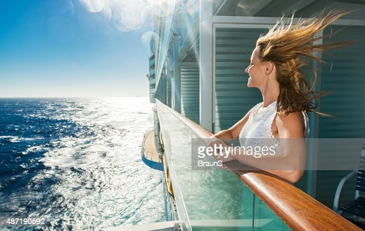 Happy woman looking at sea from a cruise ship.