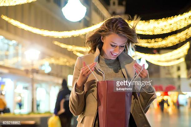 Happy Woman looking inside shopping bag with christmas decoratio