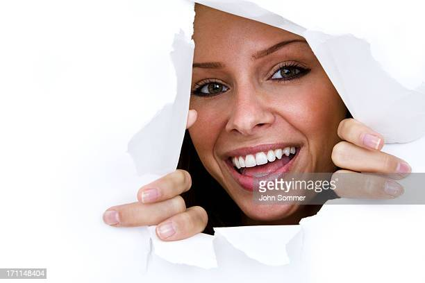 Happy woman looking through torn paper hole