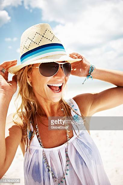 A happy woman on a beach with a hat