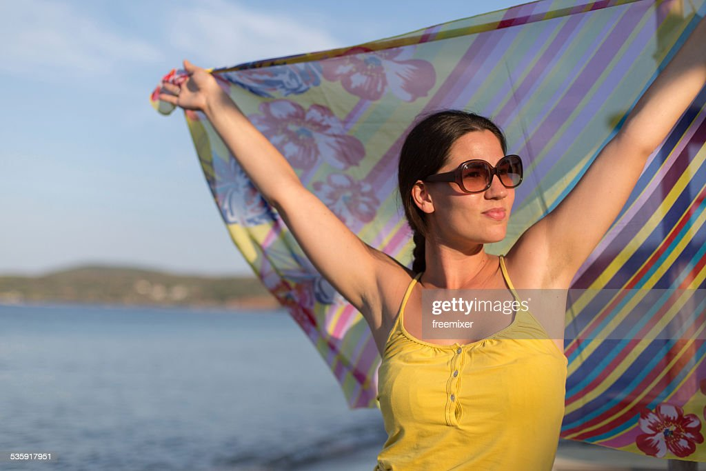 Happy woman on beach with scarf : Stock Photo