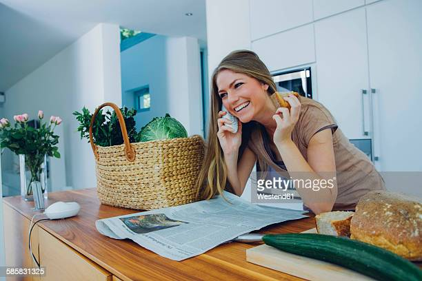 Happy woman on phone in kitchen taking groceries from bag