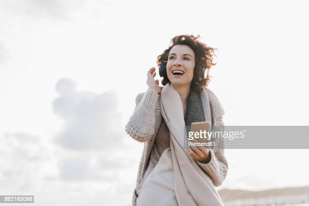 Happy woman on the beach with cell phone and headphones