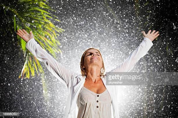 Happy woman on tropical rain.