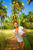 Smiling woman on tropical vacation standing in hitch-hiking pose and holding palm leaf in her hand. Coconut palm trees and blue sky in the background.