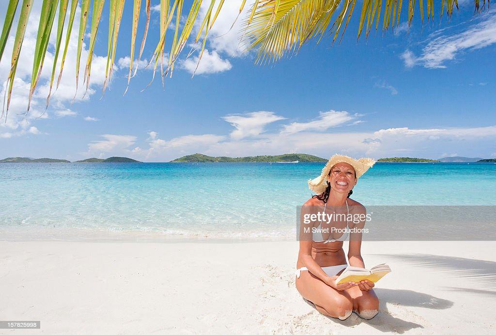 Happy woman on vacation beach reading book : Stock Photo