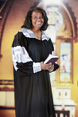 A  senior-adult woman in her black and white pastoral robe inside an old English Gothic church.