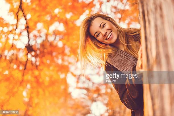 Glückliche Frau Spähen hinter dem Baum im park.