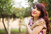 Happy young woman hugging herself in natural enviroment
