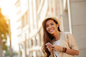 Portrait of happy young woman with smartphone in her hands