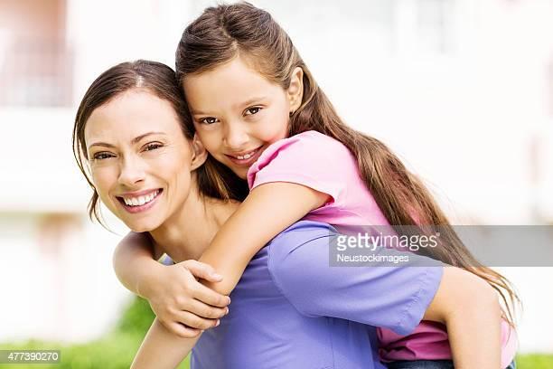 Happy Woman Piggybacking Daughter In Front Garden