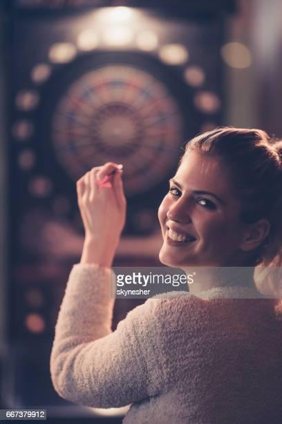 Happy woman playing darts and looking at the camera.