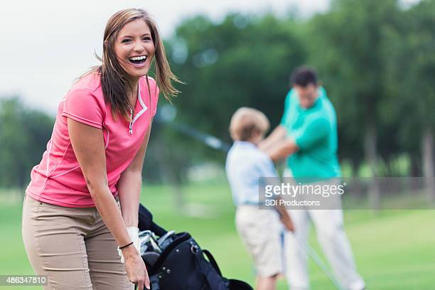 Happy woman playing golf with family on green course