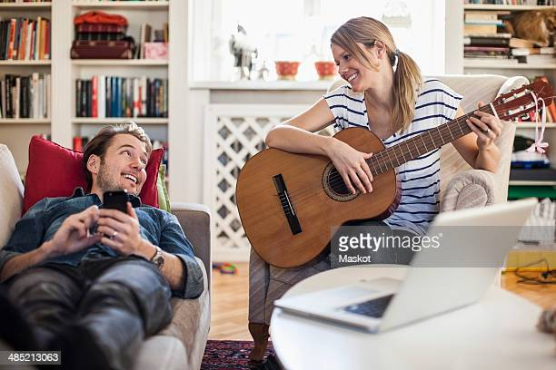 Happy woman playing guitar for man at home