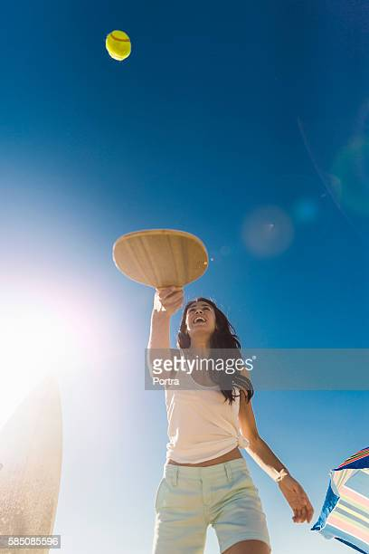Happy woman playing tennis on sunny day