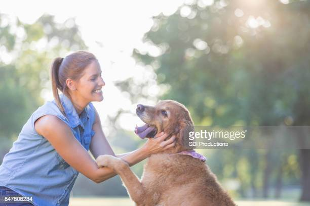 Happy woman plays with her adorable dog