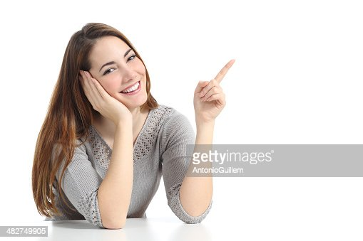 Happy woman pointing and presenting at side looking at camera : Stock Photo