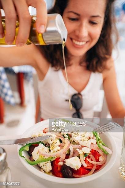 Happy woman pouring oil into salad