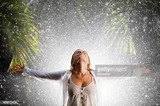 Happy woman praying during tropical rain.