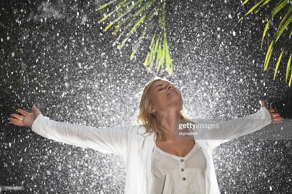 Happy woman praying during tropical rain.