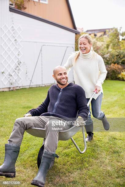 Happy woman pushing man in wheel barrow at yard