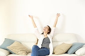 Wide angle view portrait of a happy woman raising arms and looking above on a couch with copy space