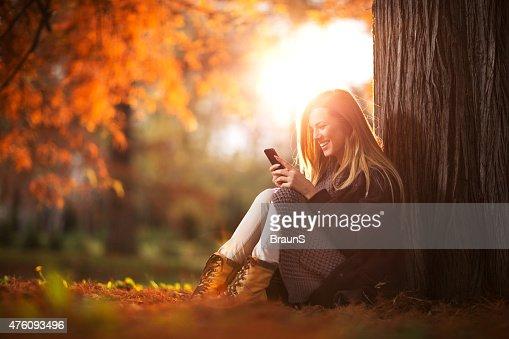 Mujer feliz leyendo un texto mensaje en el teléfono móvil.