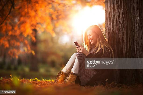 Happy woman reading a text message on mobile phone.