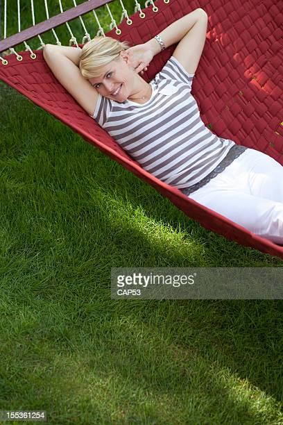 Mulher feliz relaxante em uma cama vermelha