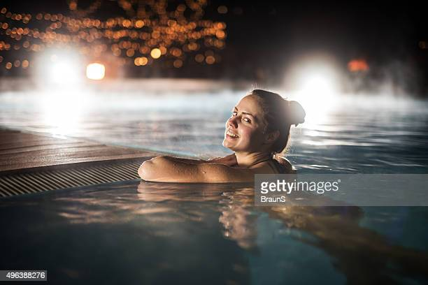 Happy woman relaxing in heated swimming pool during winter night.