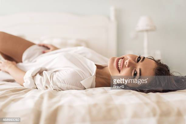 Happy woman relaxing on a bed and looking at camera.
