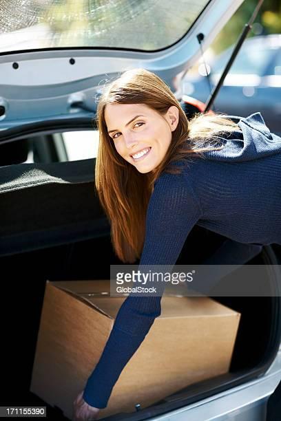 Heureuse femme enlevant boîte de voiture pendant le transfert de chez vous