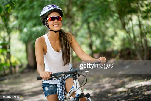 Happy woman riding a mountain bike : Stock Photo