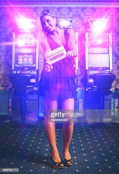 Happy Woman Showing a Gaming Voucher at Casino