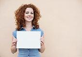 Beautiful woman showing blank white sign