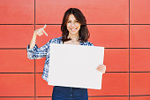 Beautiful woman pointing at blank white sign