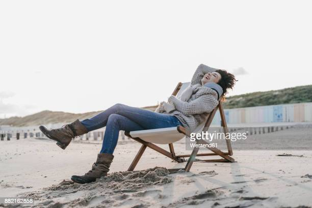 Happy woman sitting on deckchair on the beach